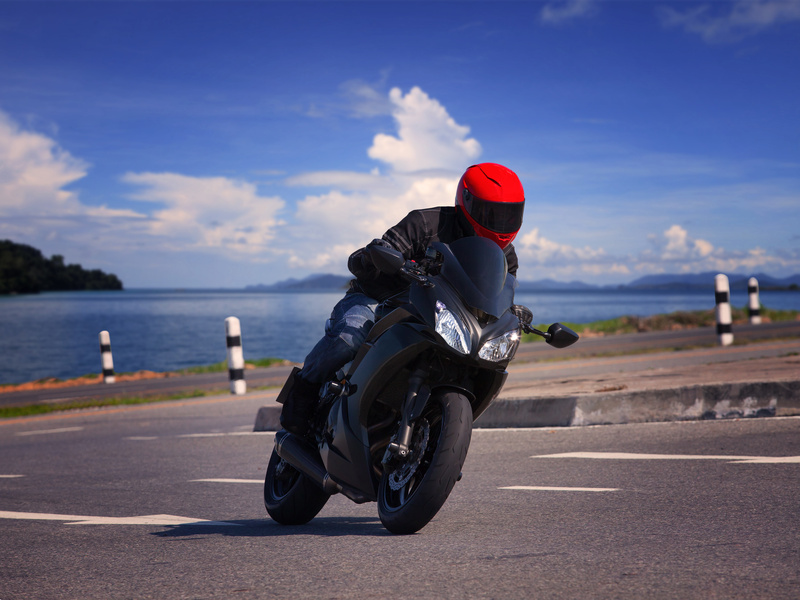 young biker man riding motorcycle on asphalt road against beautiful sea water background
